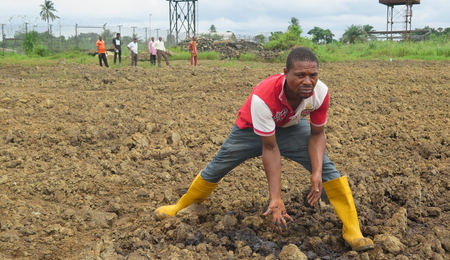 Man stands over contaminated soil in the Niger Delta