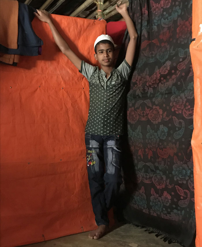 A 16 year old Rohingya boy stands against an orange wall, wearing blue jeans, a grey shirt and a white kufi.