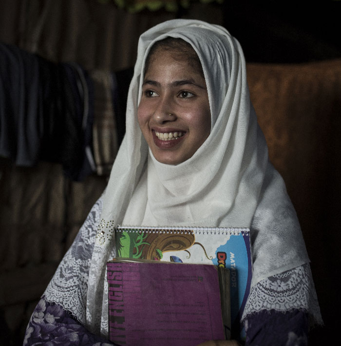 A young Rohingya girl names Lucky sits in her home wearing a white hijab and a purple top. She is holding 2 school books.