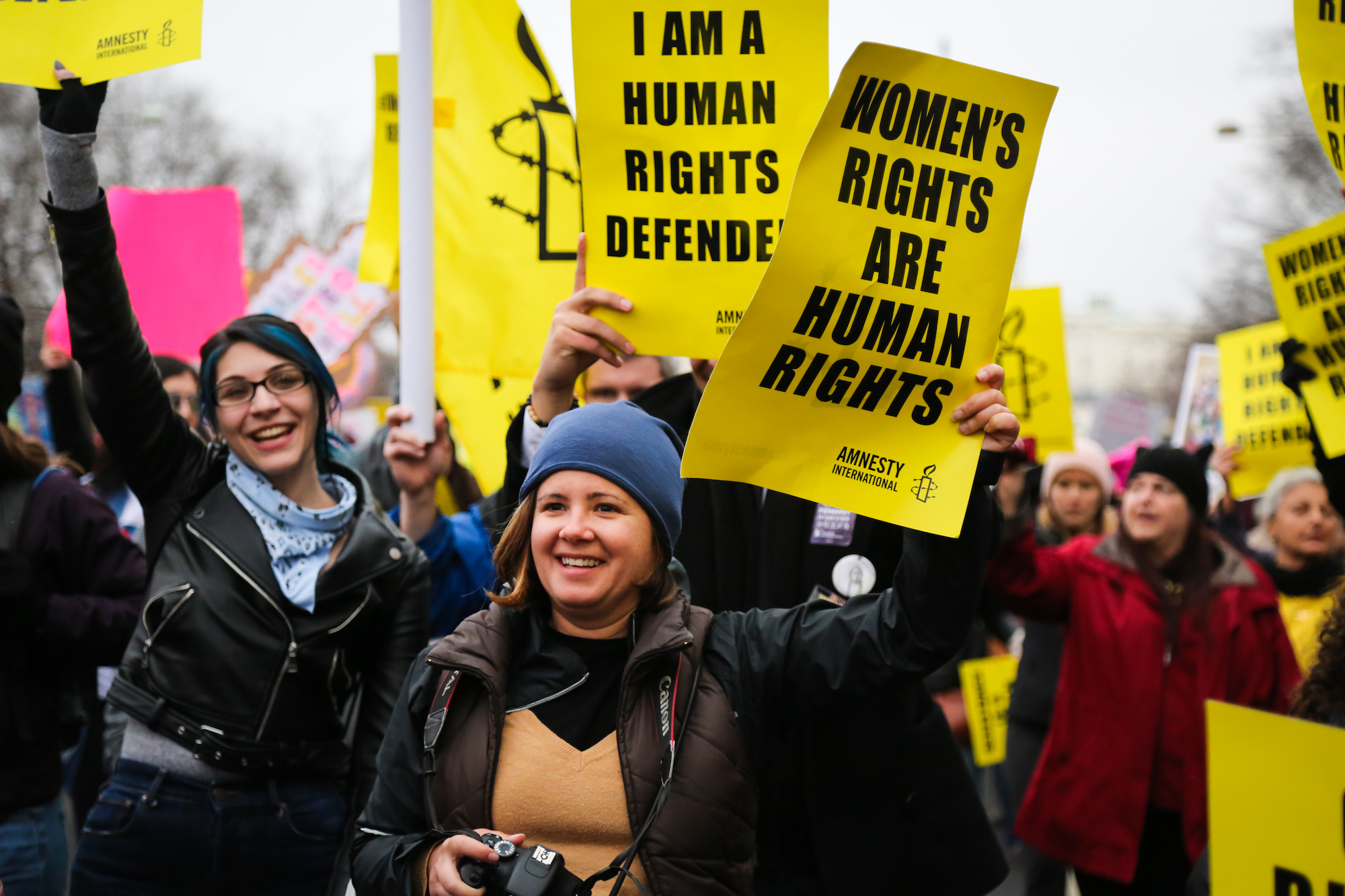 Women protesting at a rally; sign says women's rights are human rights