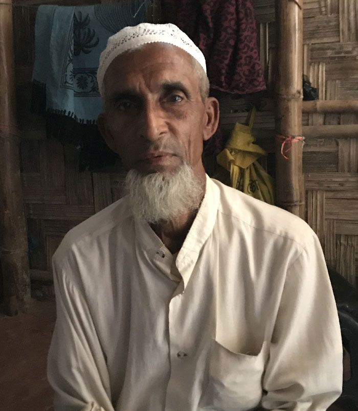An older Rohingya man named Sayed Alom sits in his home, wearing a white kufi and a white shirt.