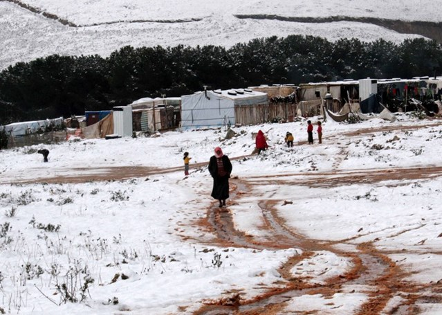 A woman walks through the snow in a Syrian refugee camp in Marj al-Khawkh, southern Lebanon, 9 January 2015. © AFP/Getty Images