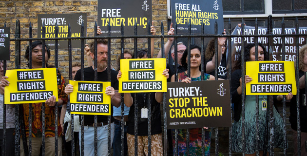 Amnesty supporters stand with signs protesting the imprisonment of Amnesty Turkey staff